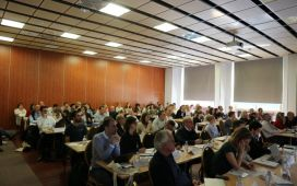 A crowded conference room with about 100 participants registered for the meeting